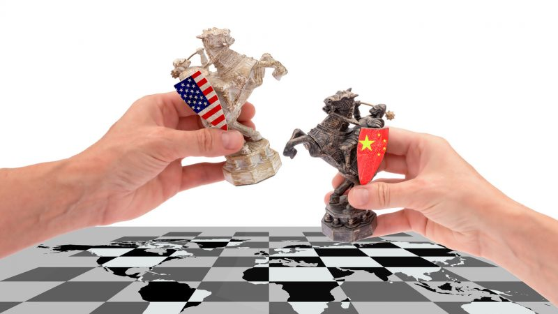 Trade war between USA and China. hands hold two chess pieces of a horse, with american and chinese flags placing them on a chessboard with a world map, isolated on a white background with copy space.